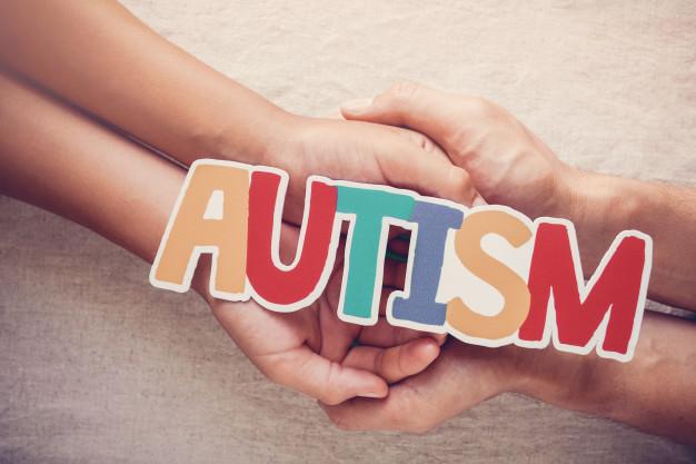 Mani che tengono la parola autismo